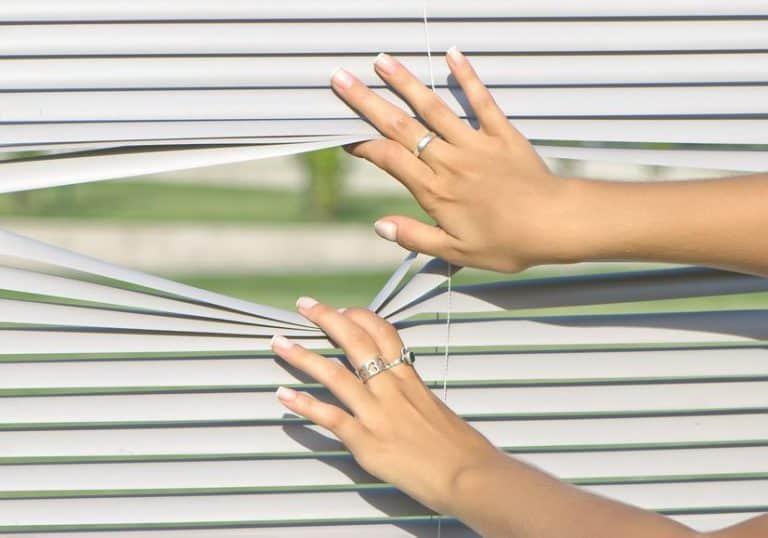 Mujer abriendo persianas