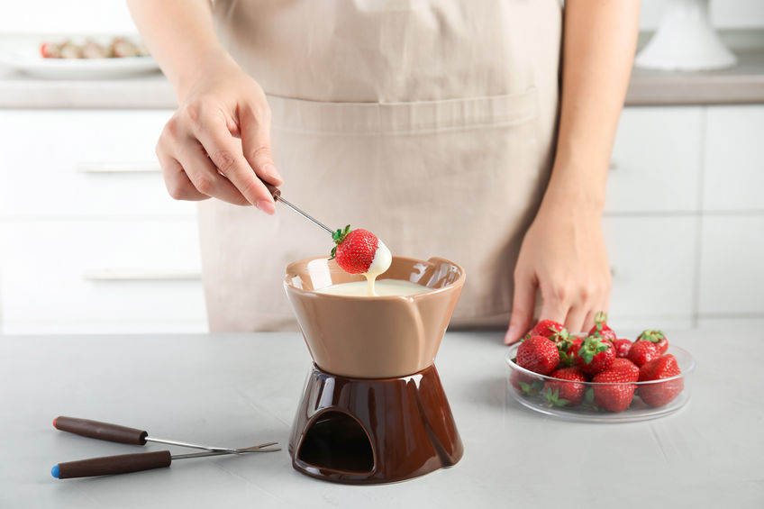Woman dipping ripe strawberry into bowl with white chocolate fondue on table