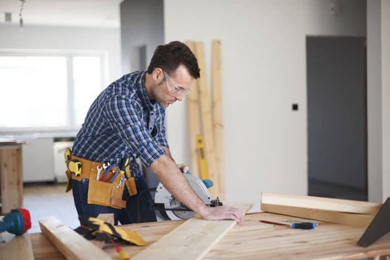 Un hombre usando una sierra y cortando madera
