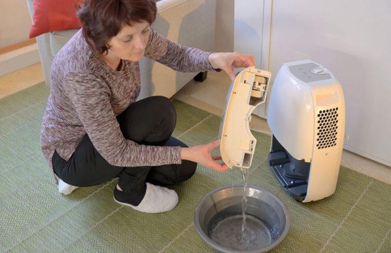 Mujer evacuando el agua de su deshumificador