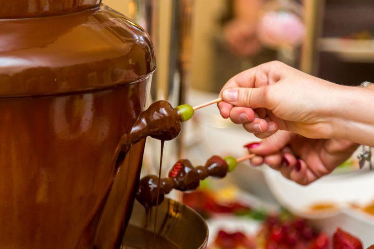 Persona bañando uvas en fuente de chocolate