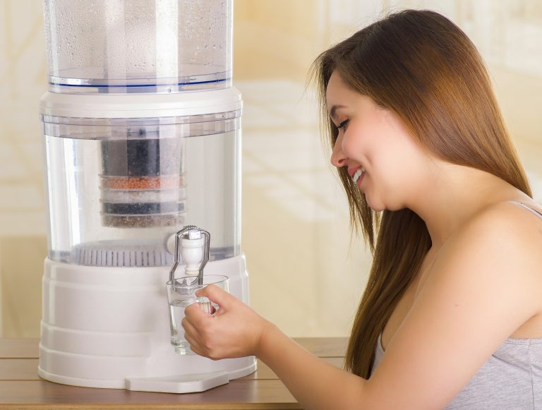 Mujer tomando agua de purificador