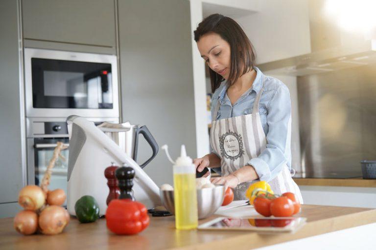 Mujer Cocinando la cena en robot de cocina