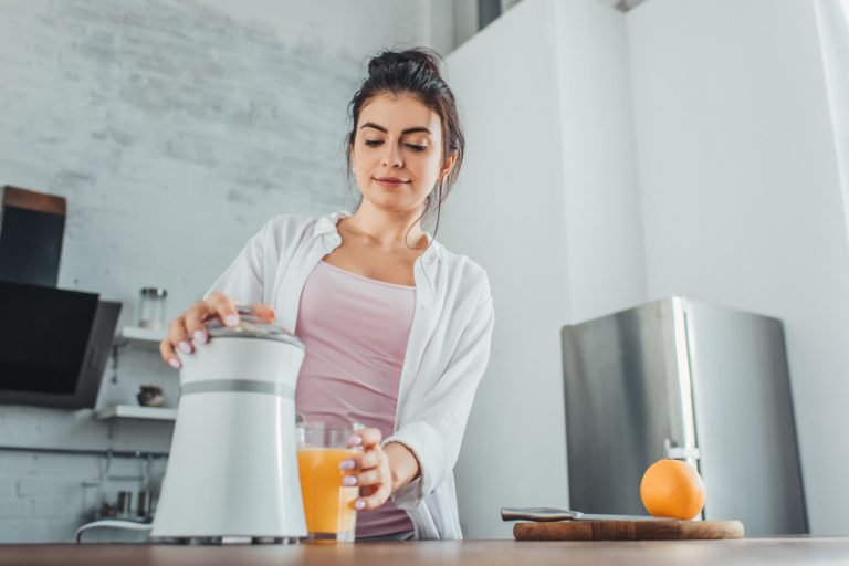 Mujer exprimiendo naranjas