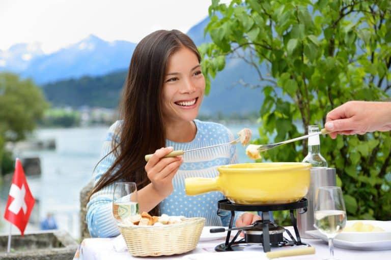 Una chica comiendo y encima de la mesa una fondue