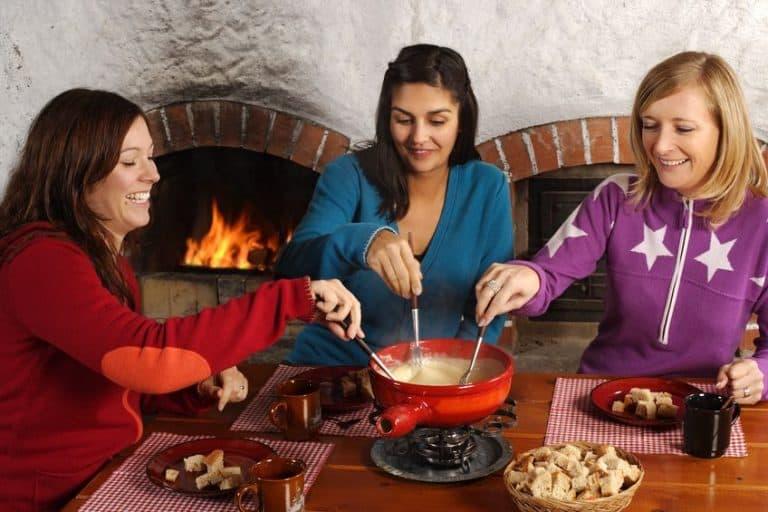 Tres chicas comiendo con una fondue de queso