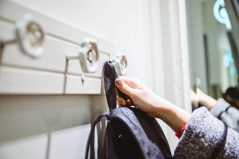 Mujer colocando su mochila en perchero