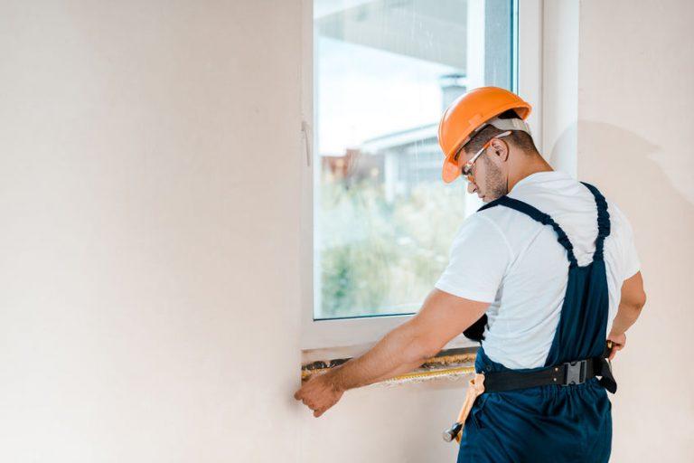 Un trabajador midiendo una ventana