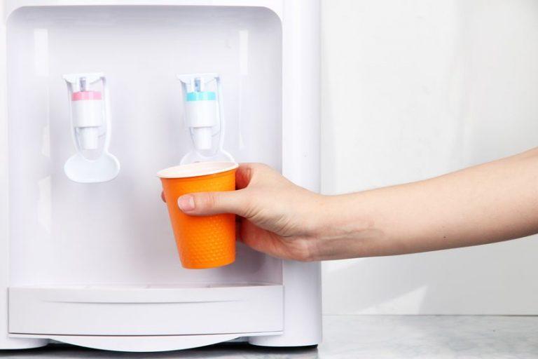 Persona tomando agua de dispensador