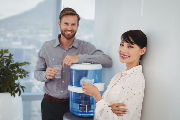 Hombre y mujer de oficina junto a dispensador de agua