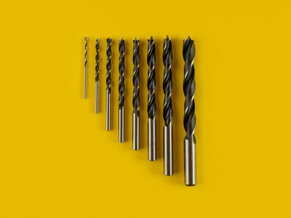 Drill bits of different sizes on yellow background,top view.Drills for wood of different sizes for a drill on an yellow background. Construction tool