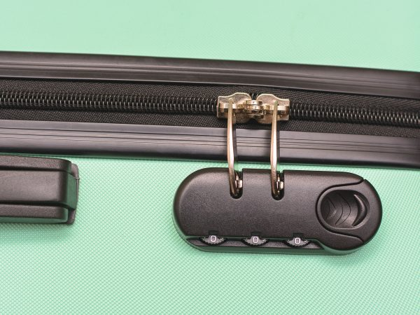 Closeup of a security padlock with three numbers on green suitcase