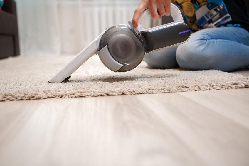 limpiando alfombra con aspiradora de mano