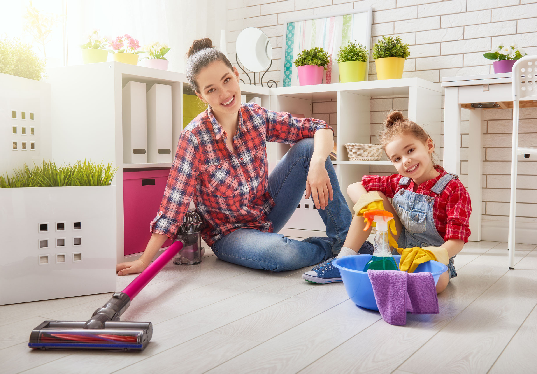 Madre e hija haciendo limpieza con aspiradora