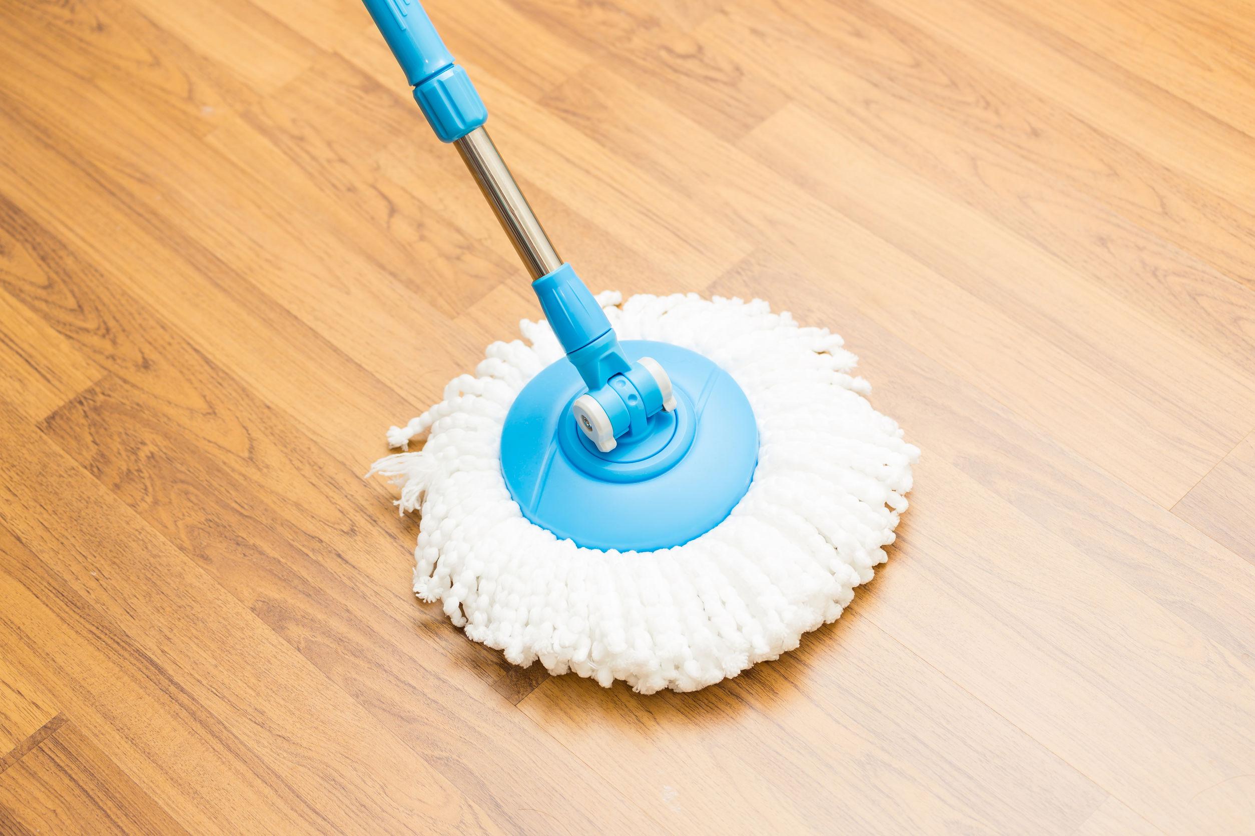 Limpieza con trapeador moderno en piso de madera laminada.
