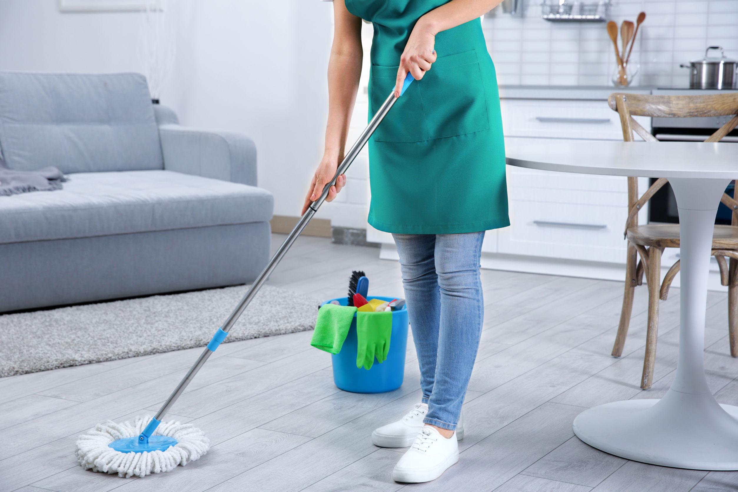 mujer limpiado el piso con fregona