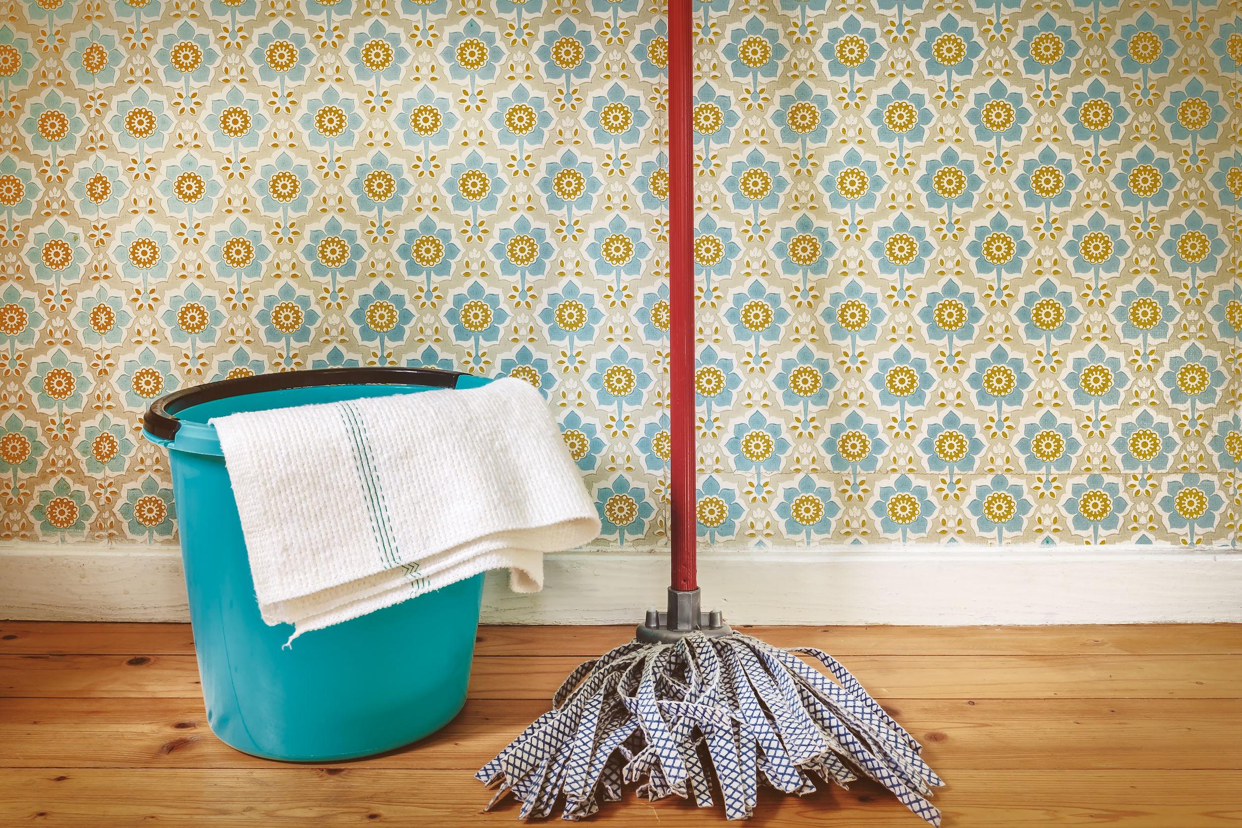 Imagen en tonos sepia de un trapeador y un balde delante del papel tapiz retro