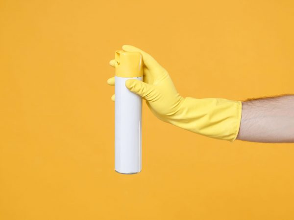 Close up of male hand in yellow gloves click on white spray bottle with cleaner liquid with place for text isolated on yellow wall background. Cleaning supplies concept. Copy space for advertisement