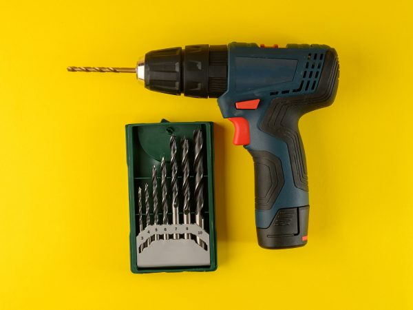 cordless drill, screwdriver with drill bit on yellow background,top view.Drill with drills of different types and sizes on a yellow background,flat lay