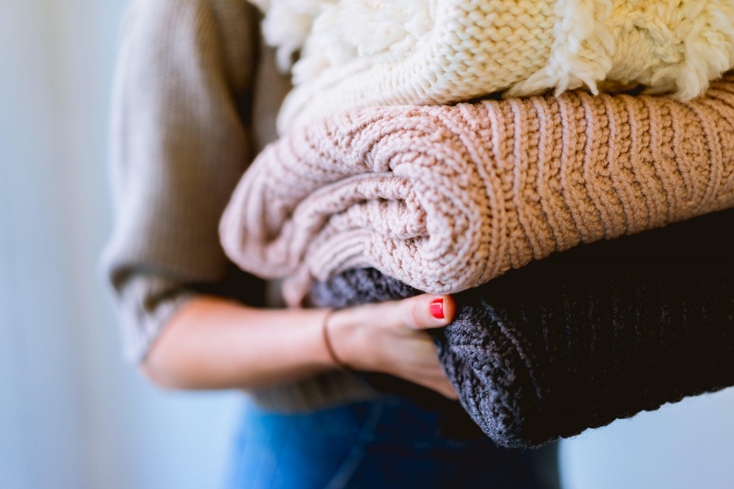 Mujer cargando ropa doblada