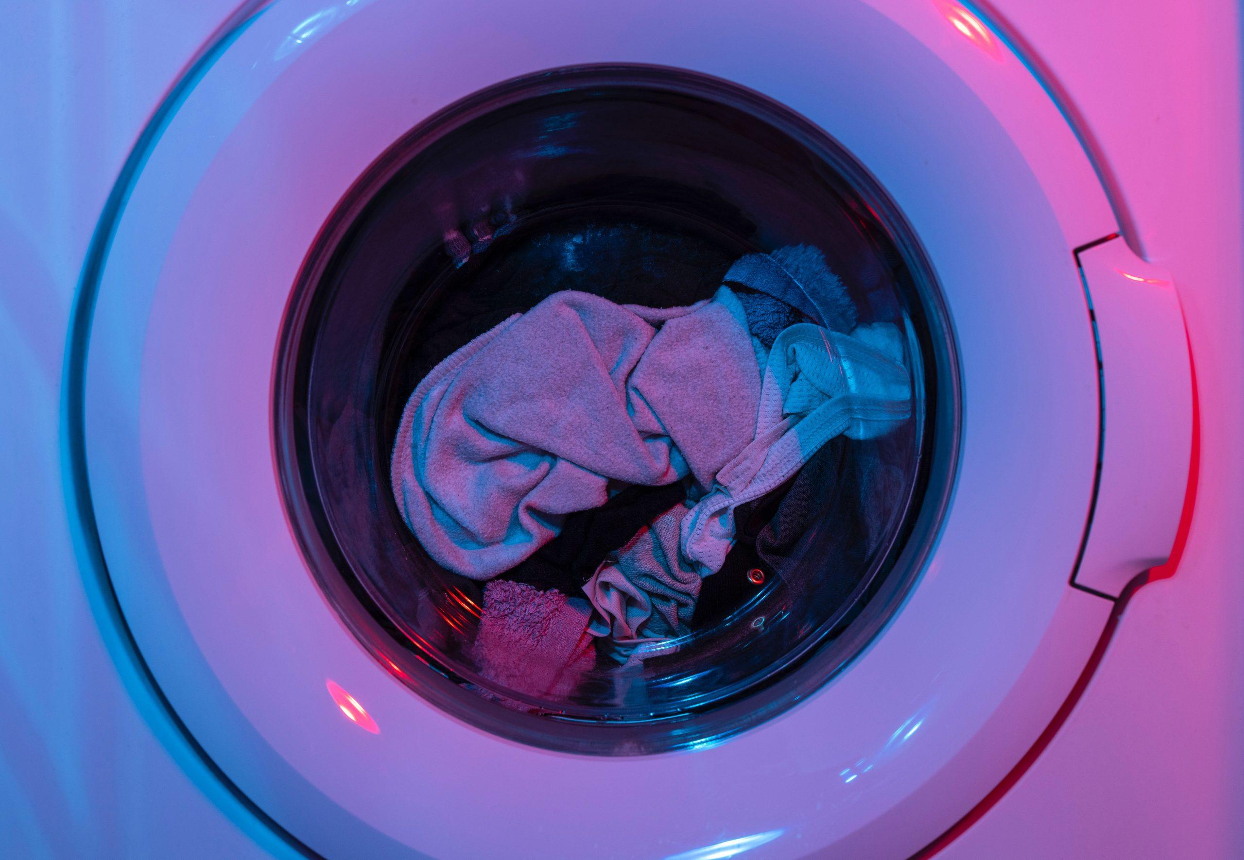 Imagen de ropa en secadora con luz morada