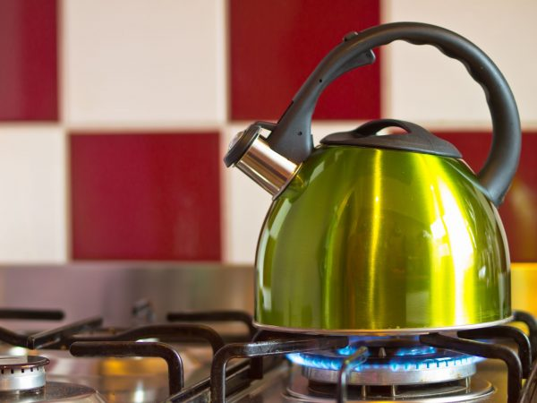 11645085 – green kettle on a modern stove in front of a red with white wall