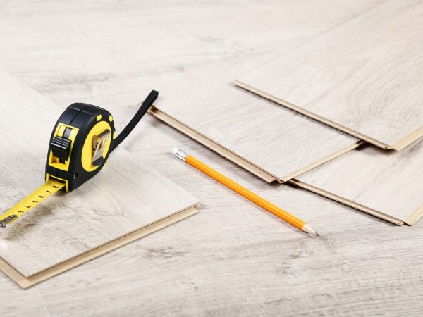 Timber laminate flooring with pencil and measuring tape