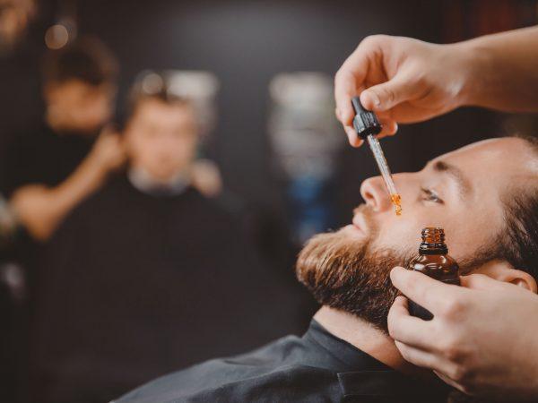 Barber aplica aceite de barba con gotero para hombre en peluquería.