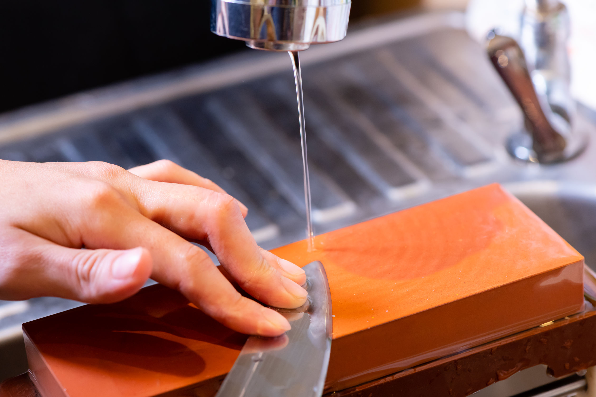 Manos de chef profesional de la mujer sostienen el cuchillo para afilar la piedra de afilar