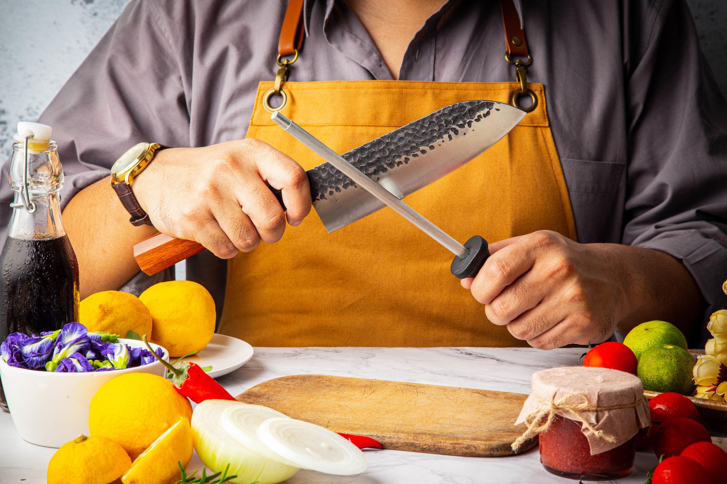 Mano masculina sosteniendo y afilado el cuchillo de Damasco de cocina japonesa