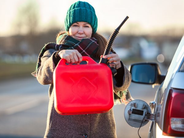 Woman a driver showing plastic can due tank empty of petrol, a person standing close to opened cap, winter season