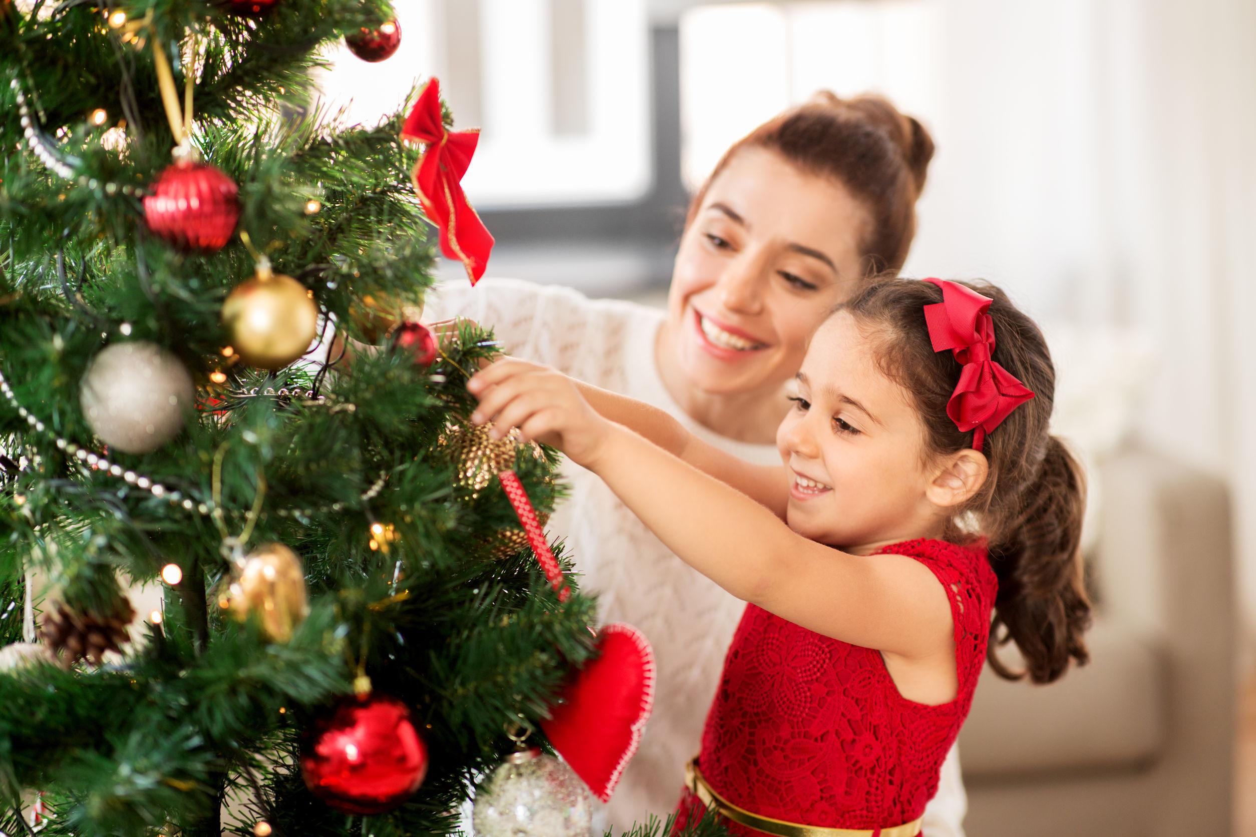 feliz madre e hija decorando el árbol de Navidad en casa