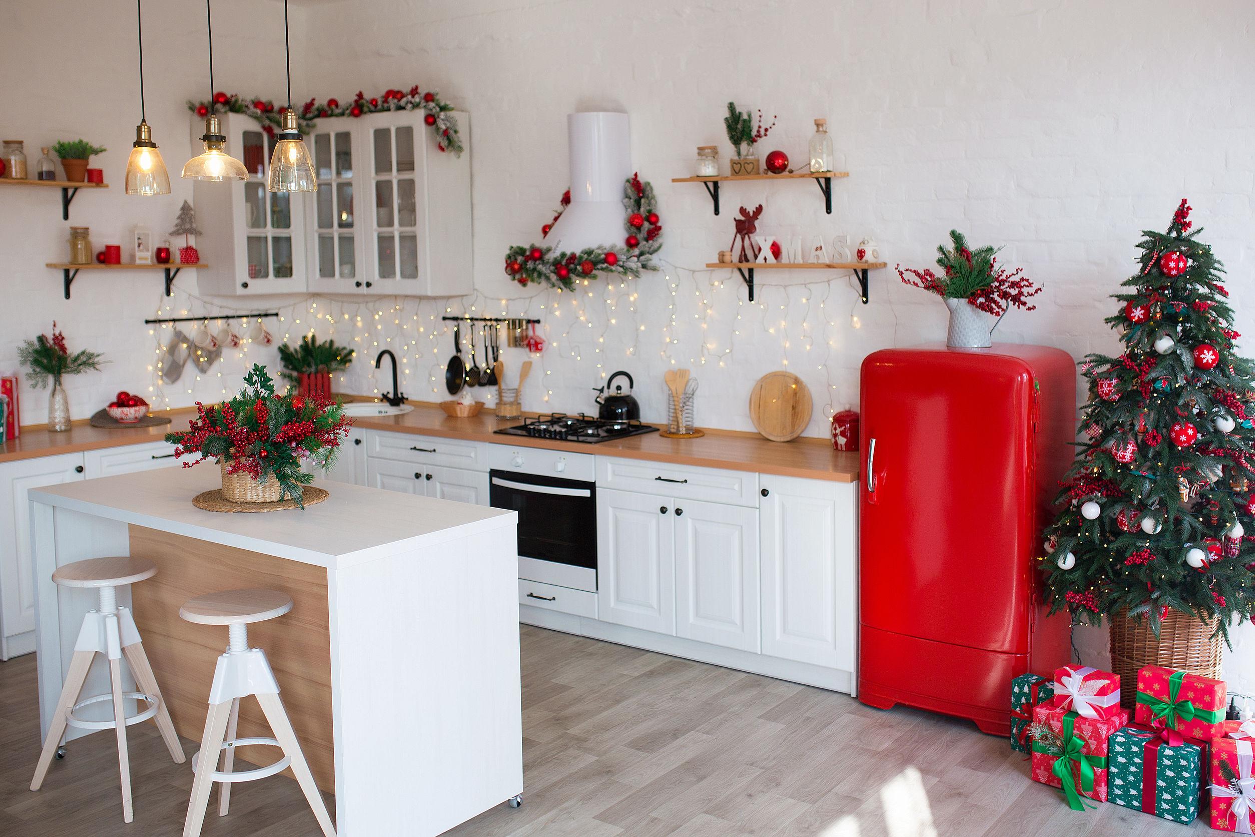 Interior de cocina moderna con isla, fregadero, gabinetes en nueva casa de lujo decorada en estilo navideño