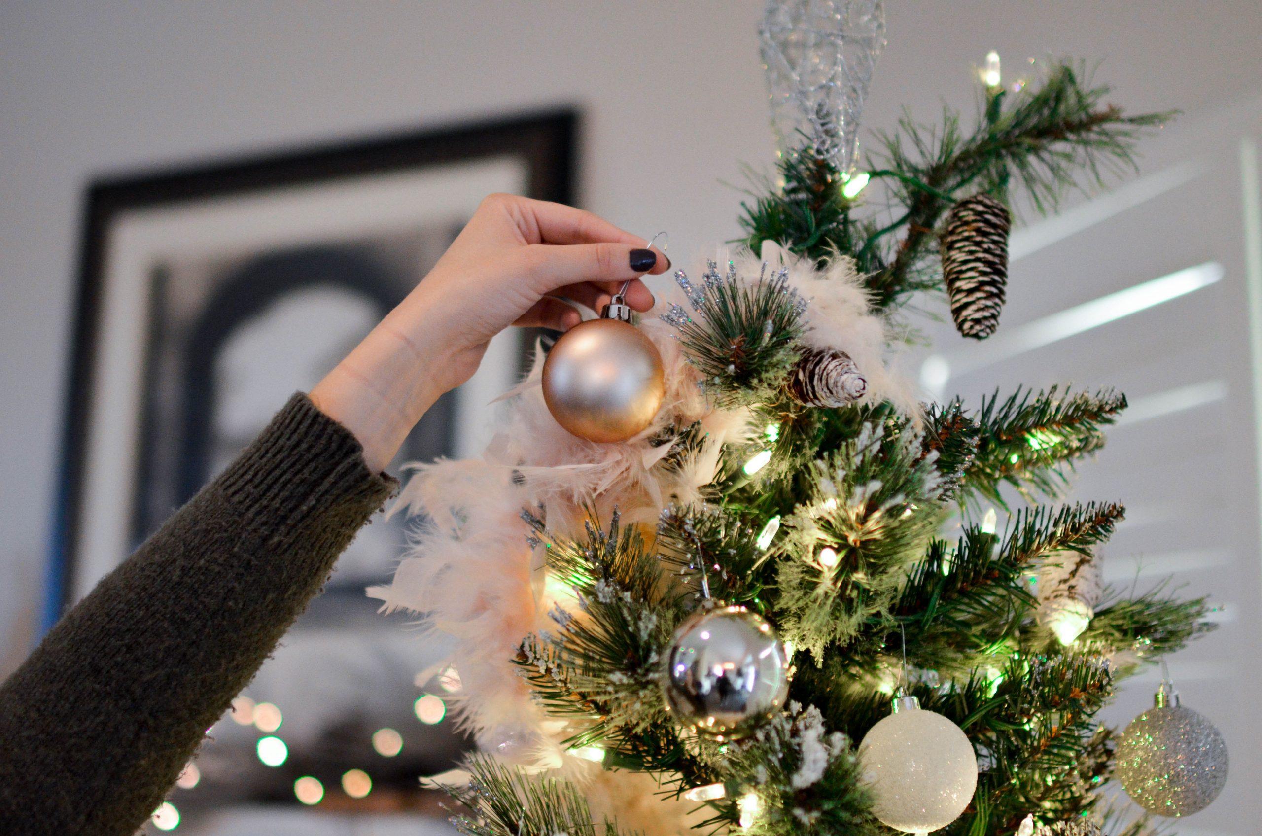 Mano de mujer colocando bonba de decoracion en arbol de navidad