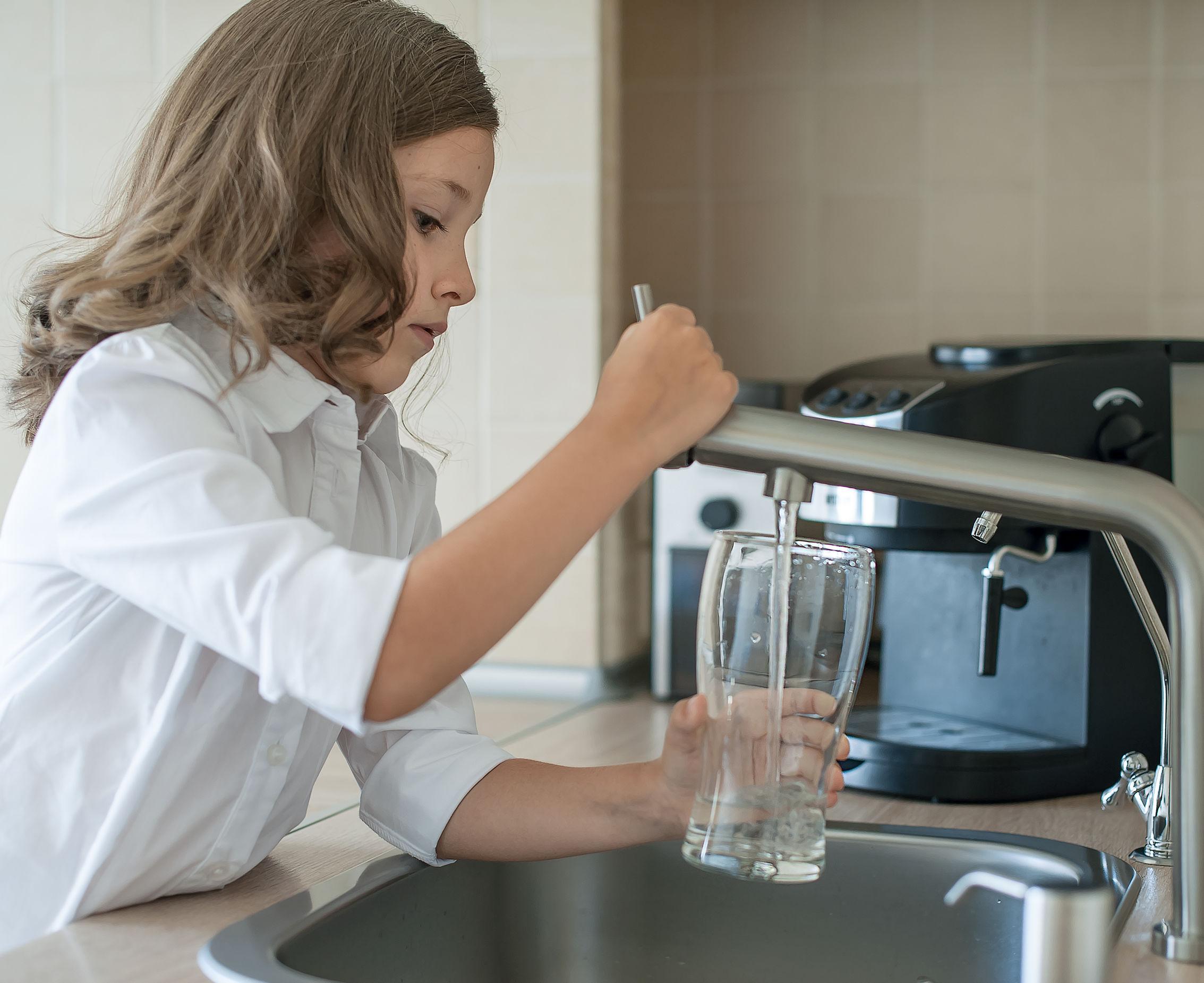 Retrato de una niña caucásica ganando un vaso de agua limpia del grifo.