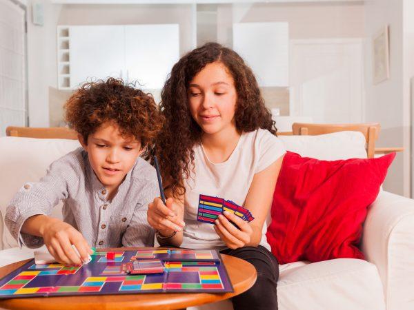 Una adolescente y una niña jugando juegos de mesa juntos en casa