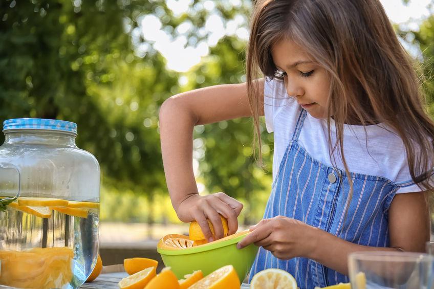 niña exprimiendo naranjas