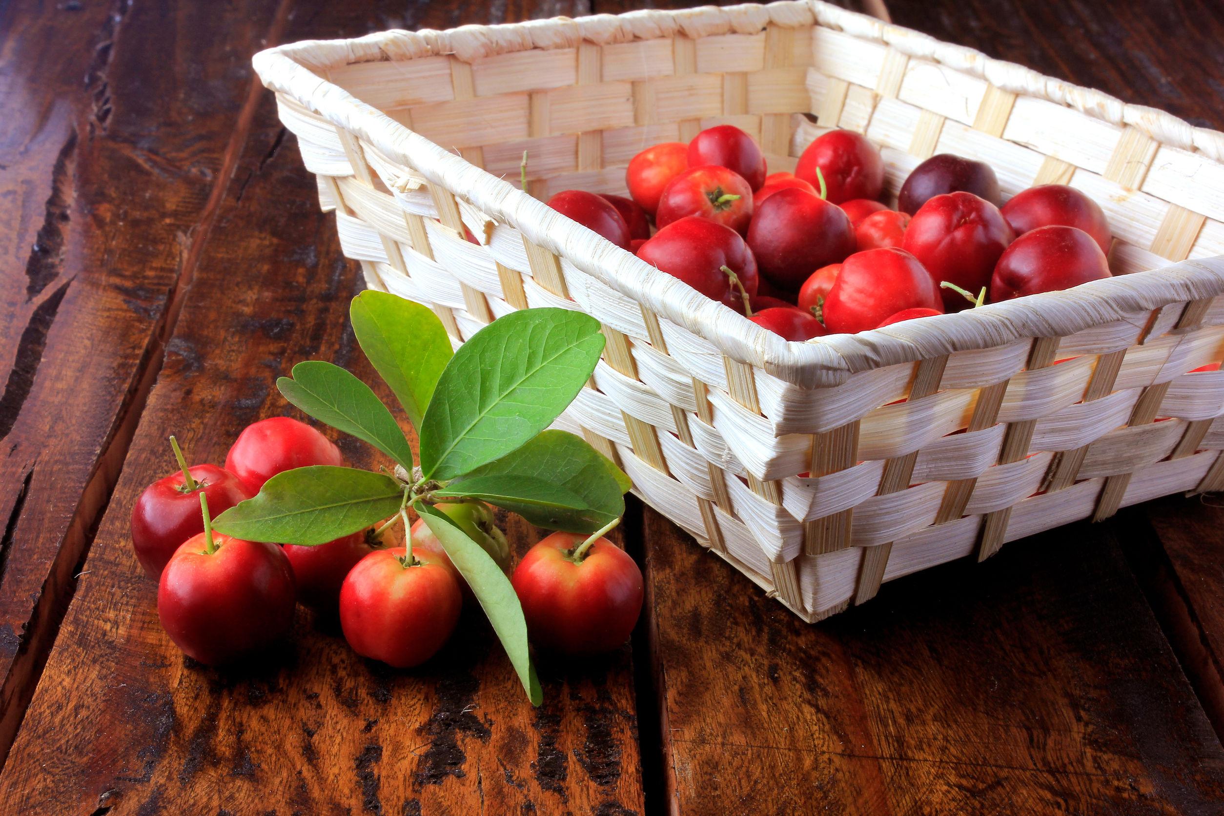Acerola Cereza cruda, fresca, caja sobre mesa de madera rústica, frutas antioxidantes. Vitamina C alta