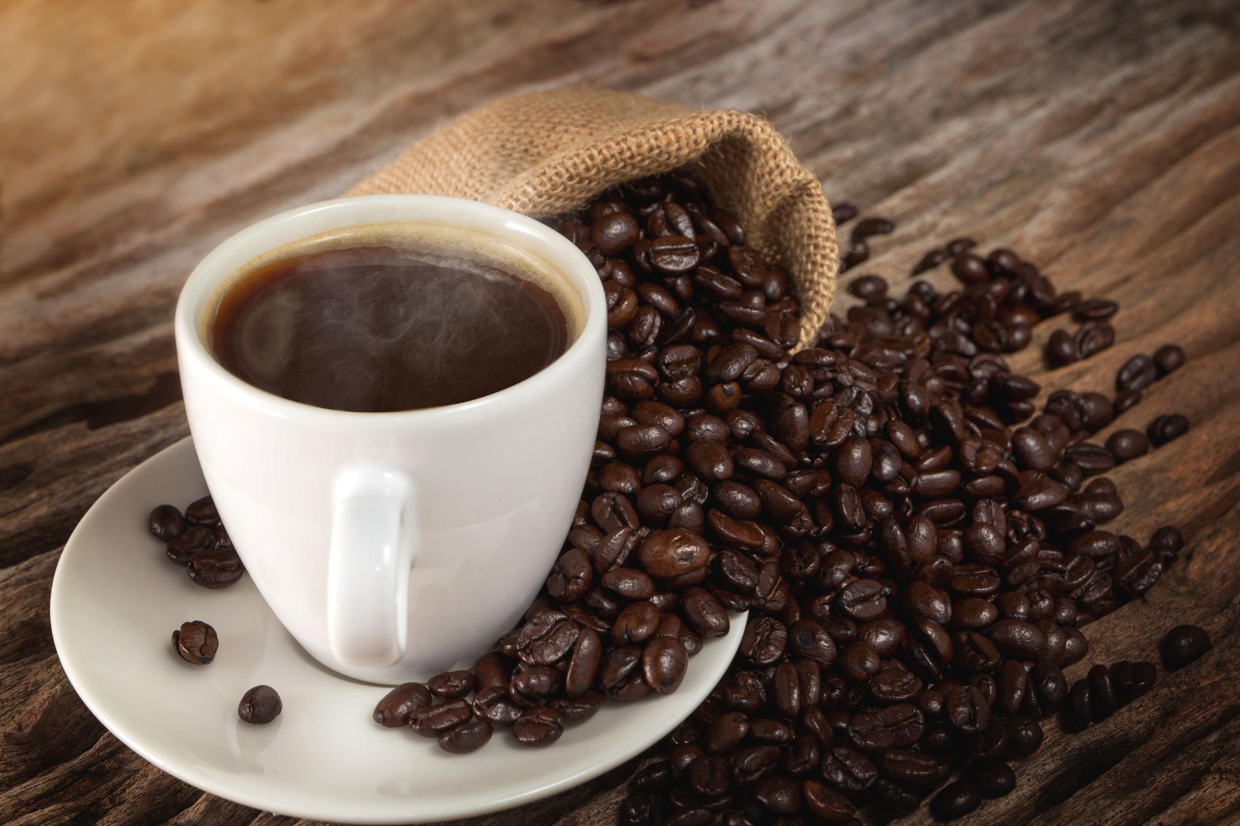 Una taza de café caliente en una mesa de madera con granos de café tostados