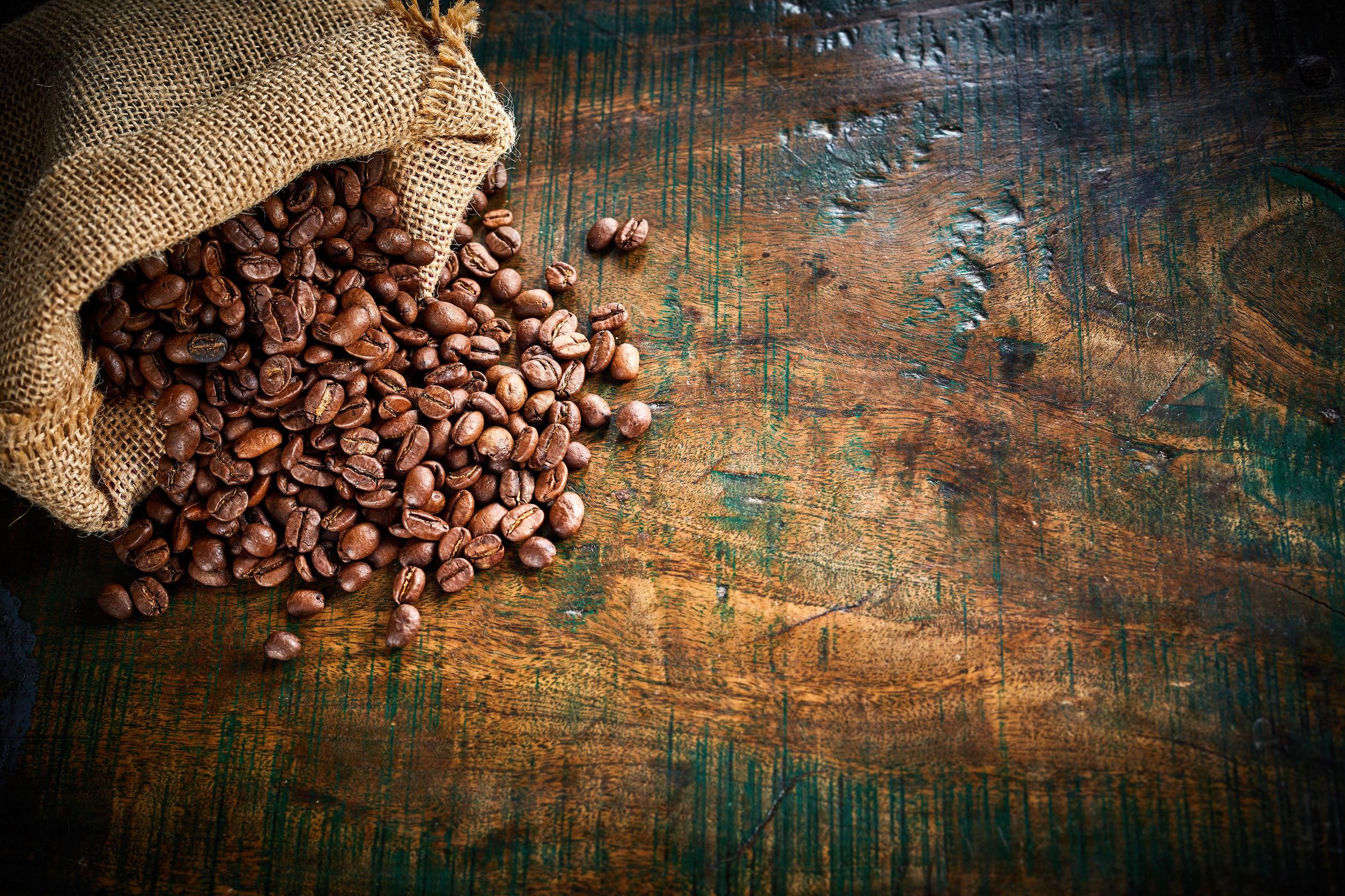 Pequeña bolsa de arpillera de granos de café tostados frescos que se derraman sobre una vieja superficie de madera