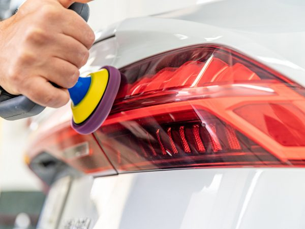 manual polishing of the headlight of luxury cars with the application of protective equipment.