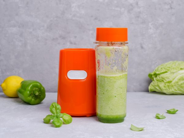 Cooking green vegetable smoothies in kitchen appliances. Grey slate background. Selective focus.