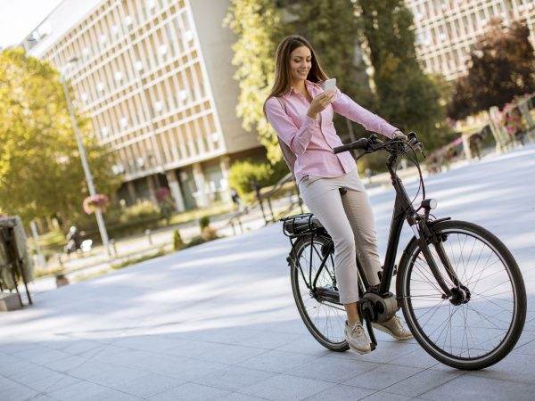 Pretty young woman riding an electric bicycle and using mobile phone in urban environment