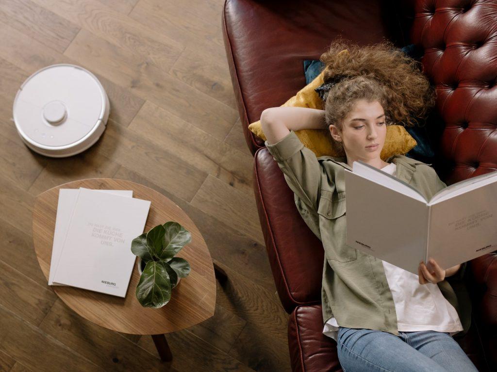 aspirador Roomba limpiando mientras una chica está leyendo