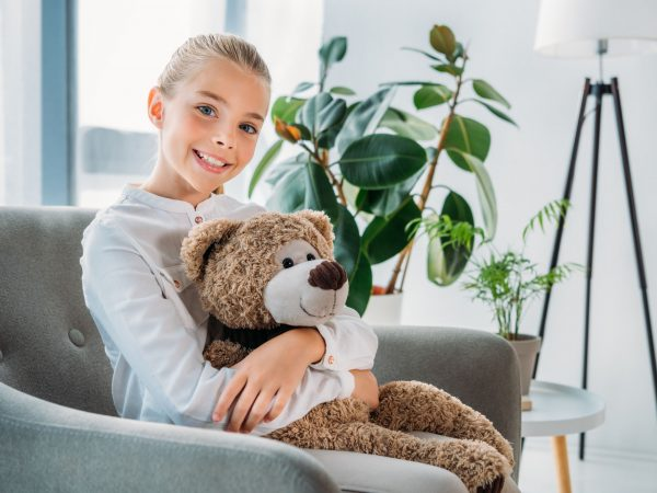 adorable little child embracing her teddy bear while sitting in armchair and looking at camera