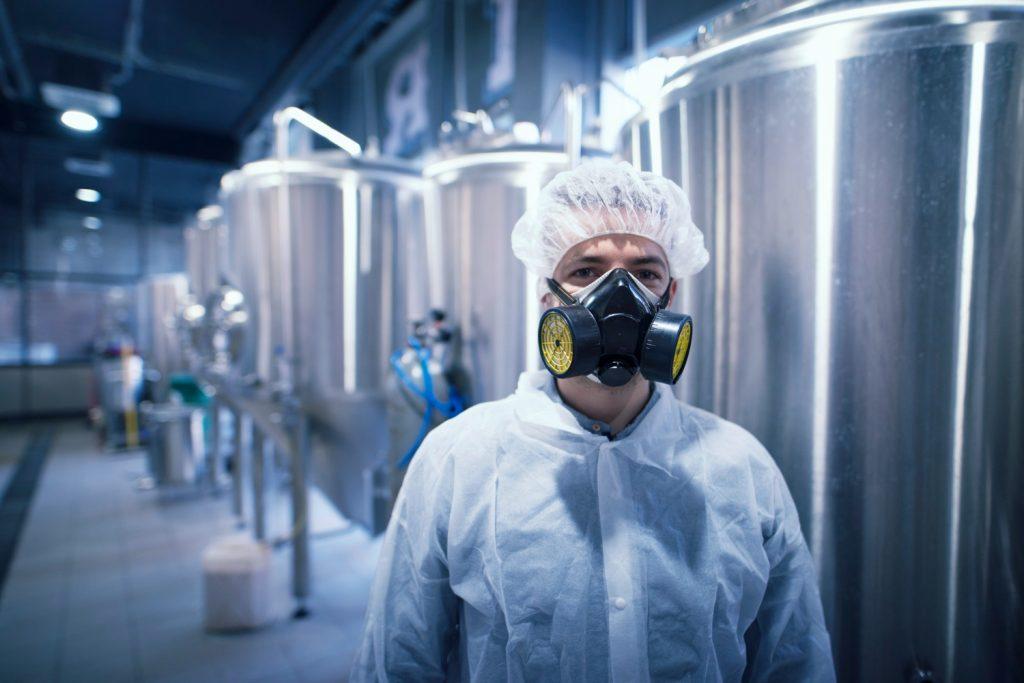 hombre con mascara de gas en fabrica industrial