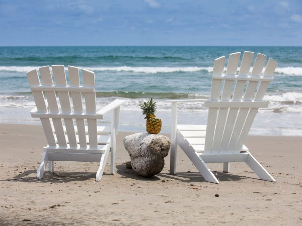 Empty white wooden chairs at a paradisiac beach on the tropics in a beautiful sunny day
