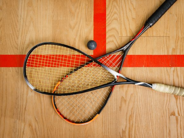 Two squash rackets and ball on court floor, top view, nobody, game concept. Active sport hobby, fitness workout for healthy lifestyle