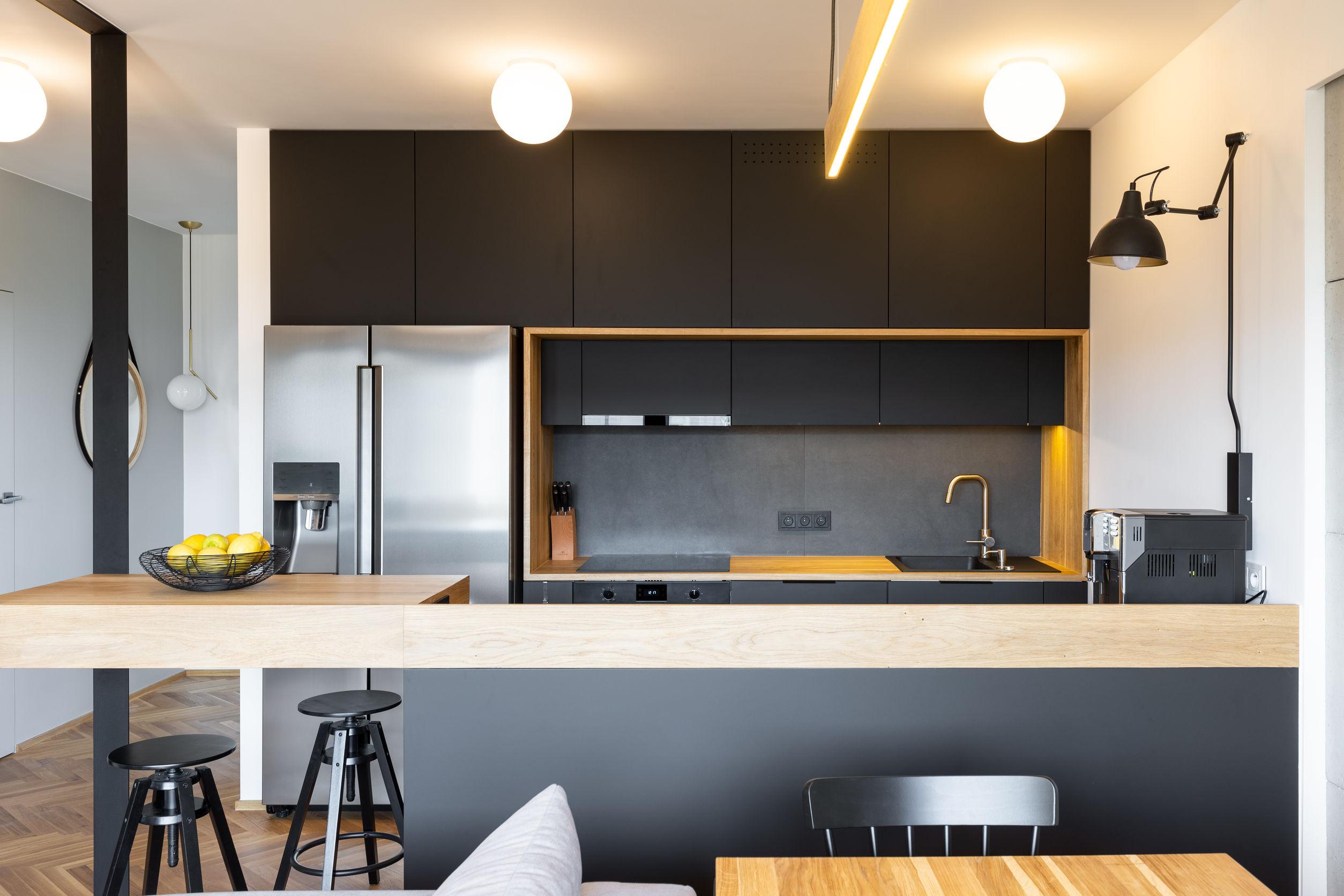 Muebles de madera negra y una lámpara industrial sobre una máquina de café en un hermoso y moderno interior de cocina con comedor.