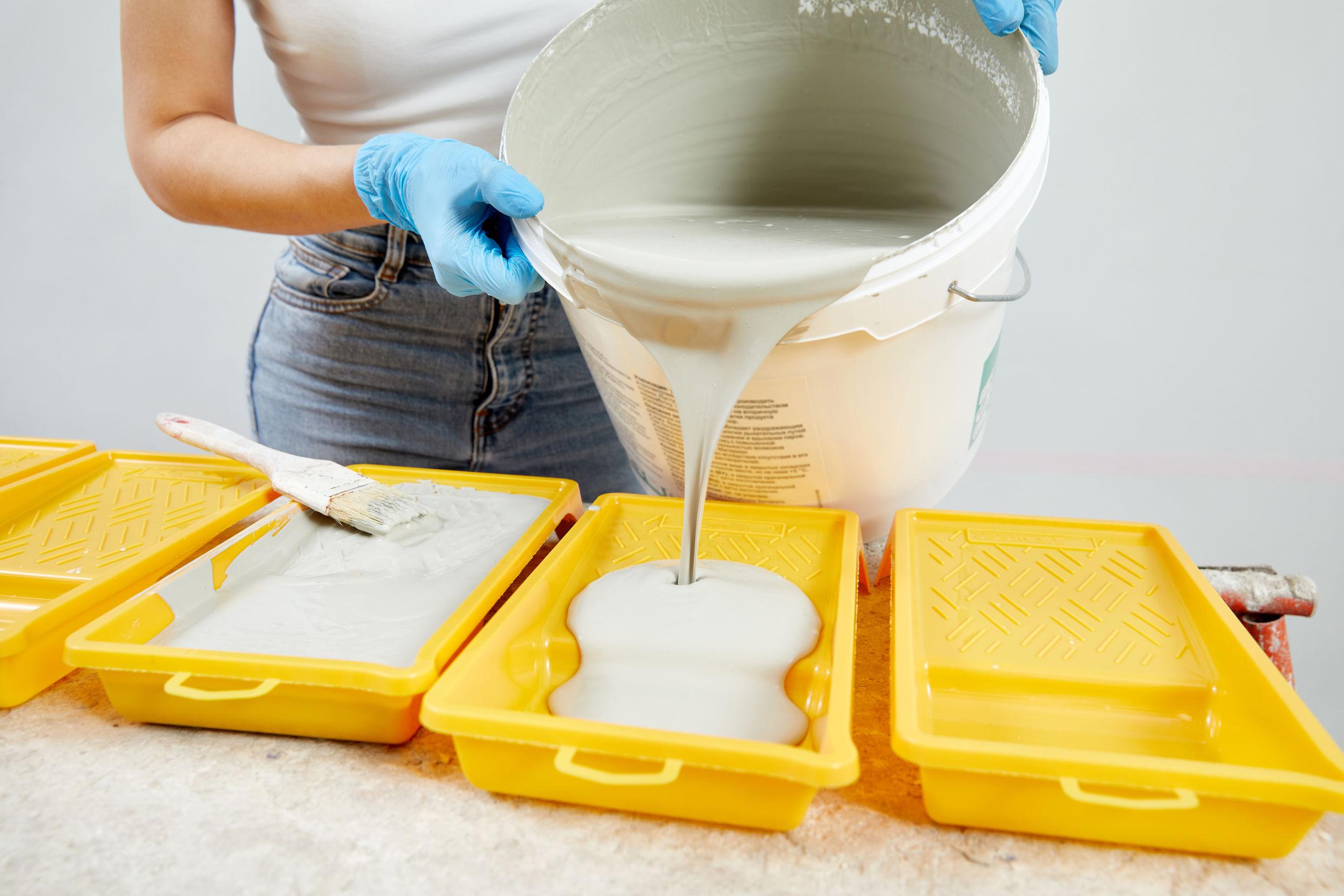 Mujer joven vertiendo pintura en la bandeja de pintura plástica